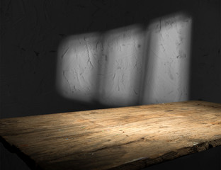 Wall Mural - Old wood table with blurred concrete block wall in dark room background.