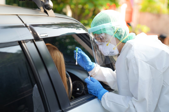 Doctor or nurse wearing PPE, N95 mask, face shield  and personal protective gown standing beside the car/road screening for Covid-19 virus