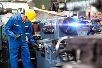 Mechanical Engineering control lathe machine in factory facility. Safety First at work place.
