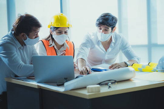 Team of engineer and architects working,discussing,designing, planing, measuring layout of building blueprints at workplace.wearing mask for protect pm2.5 and stop corona virus outbreak.