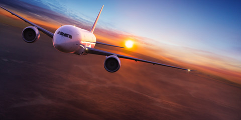 Poster Airplane Commercial airplane jetliner flying above dramatic clouds in beautiful light. Travel concept.