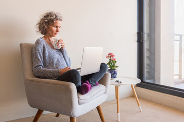 Middle aged woman working from home with cup and laptop - self isolation concept (selective focus)
