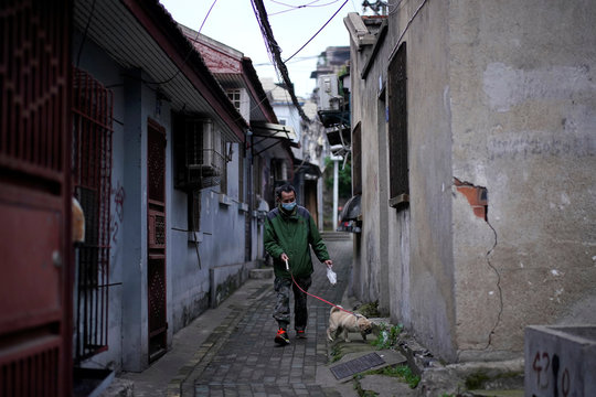 Man wearing a face mask walks a dog at a blocked residential area after the lockdown was lifted in Wuhan, capital of Hubei province and China's epicentre of the novel coronavirus disease (COVID-19) outbreak