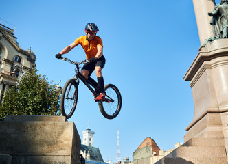 Young cyclist performing dangerous jumps on mountain bike on stairs of monument pedestal over blue sky, concept of extreme sport