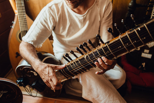 Close up photo of hands of an Indian musician playing a sitar