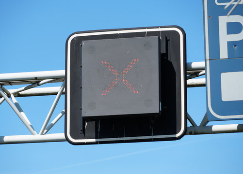 Matrix sign with a red cross above a highway in the Netherlands.