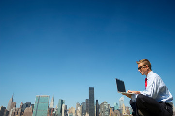 Businessman in a suit sitting outdoors using laptop computer above the city skyline under clear blue sky copy space