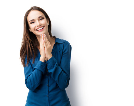 Portrait of happy gesturing smiling brunette lovely woman in casual smart blue clothing, isolated against white background. Caucasian brunette model in emoshions and feeling concept.