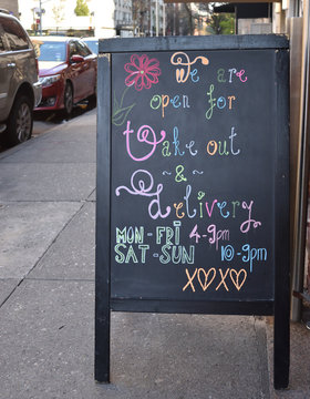 Blackboard sign reading We Are Open For Take Out & Delivery handwritten in colorful curly chalk script with drawings of red flower & love symbols on city sidewalk, April 7, 2020, in New York.