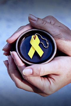 Cropped Hands Holding Yellow Ribbon On Container