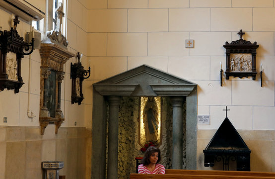 A woman prays during an Easter mass led by Bishop Krikor Kousa at the Armenian Catholic Church as Egypt ramps up efforts to slow the spread of the coronavirus disease (COVID-19), in Cairo