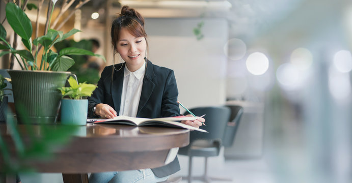 Young woman asian with laptop online learning. Lifestyle social distance education. Development skills by yourself. Lady asian in workplace office modern business. Green corporate environment.