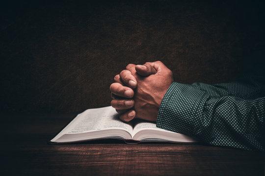 Hands of a man praying over an open bible