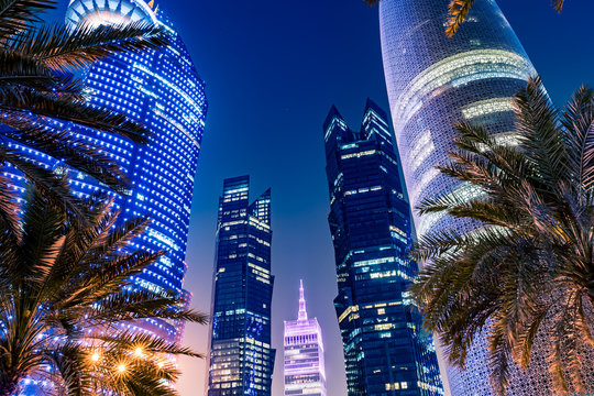 Night view on the centre of the city Doha, Qatar with many modern luxury building and skyscrapers illuminated with numerous lights. Close-up shot