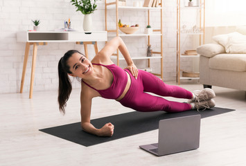 Sporty lady working out at home with online fitness course