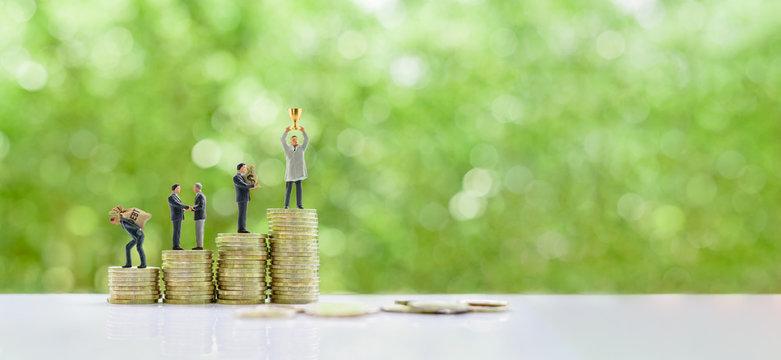 Miniature figurine businessman bears a burden of debt, make a deal, holds a money bag, raise a gold trophy cup on stacks of coins