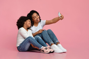 Family Selfie. Cheerful black mother taking photo with her little daughter