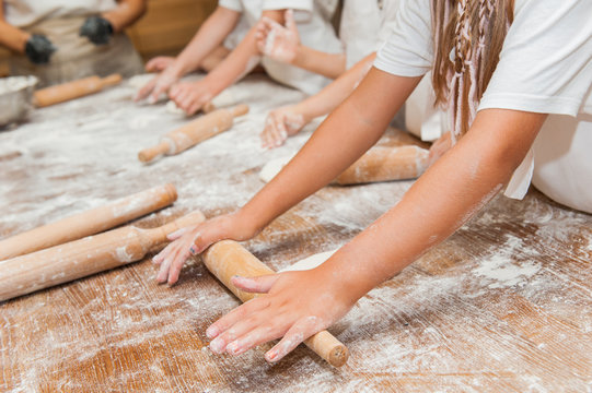 Little kids make dough products. Flour is scattered around. Hands close up.
