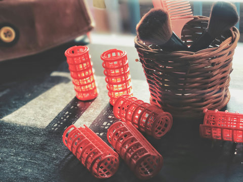 Close-up Of Red Containers With Shaving Brushes On Table