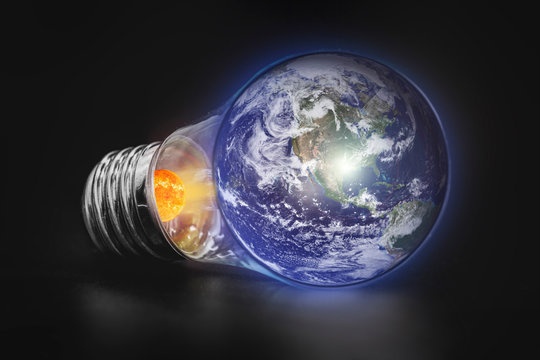 Energy Concept - Save energy, planet Earth in a light bulb on a black background
