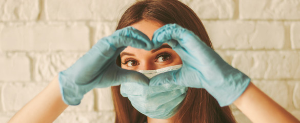Banner young woman in protective face mask and medical gloves gesturing love shape sign. Happy girl in medical face mask and gloves looking through hands in form of heart symbol. Health care, COVID-19
