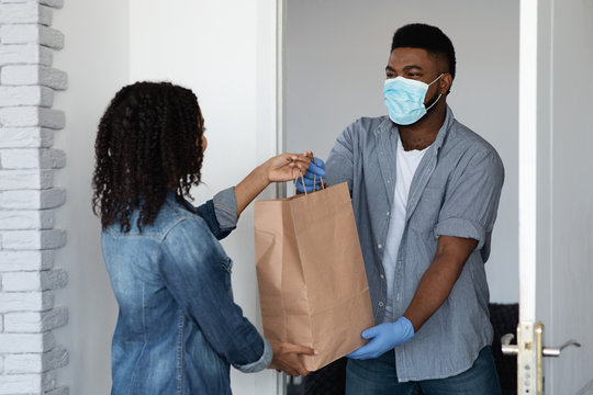 Black courier guy in medical mask delivering grocery order to woman