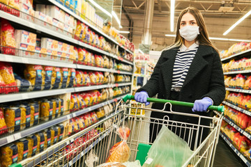 man in mask and protective gloves with cart in shop at coronavirus epidemic