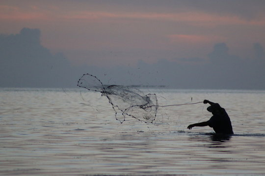 a man fishing with a cast net