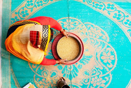 High Angle View Of Woman Cleaning Wheat At Home