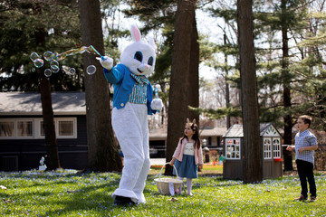 A person dressed as an Easter bunny blows bubbles with Genevieve Pina, 3, while making a surprise visit during a day full of Easter festivities, amid the ongoing coronavirus disease (COVID-19) outbreak, in Plymouth, Michigan