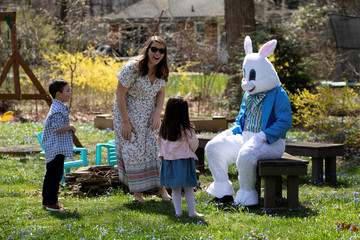 Dayna Pina smiles with her children as a person dressed as an Easter bunny makes a surprise visit to their house, amid the ongoing coronavirus disease (COVID-19) outbreak, in Plymouth, Michigan