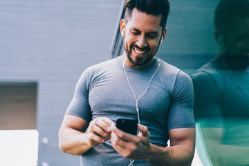 Cheerful caucasian sportsman in earphones satisfied with player on mobile phone choosing music for workout, smiling male in tracksuit using gadgets during pause on training sending mail on cellular Fotobehang