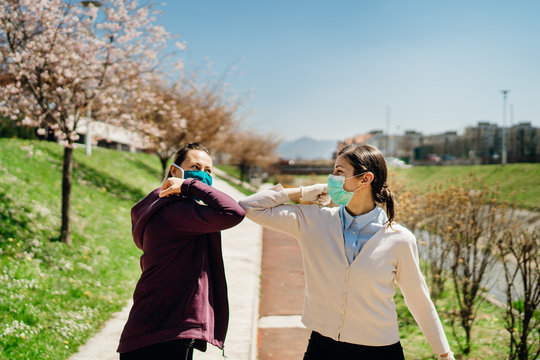 Two friends with protective masks greet with elbows.Elbow bump alternative greeting during quarantine to avoid physical contact.Coronavirus COVID-19 disease protection.Social distancing practice
