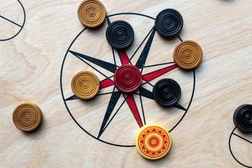 Carom board with striker and carom men. Selective focus.