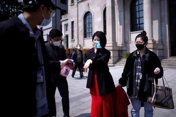 Staff members wearing face masks disinfect the hands of a bride during their wedding photo shoot after the lockdown was lifted in Wuhan