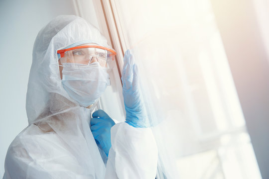 Loneliness quarantine, young woman in medical mask looks out window self isolation. Coronavirus pandemic concept
