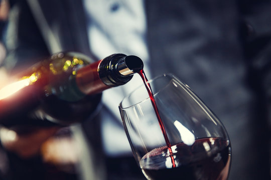 Red wine spouts into glass from bottle. Dark background