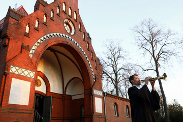Pastor Viktor Weber plays his trumpet as he celebrates the resurrection of Jesus Christ on Easter Sunday at a cemetery in Berlin