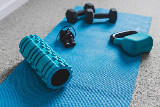 home gym concept, room with dumbbells and fitness gear on yoga mat to workout from home