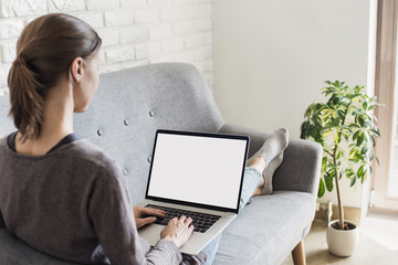 Young woman working at home, Student girl using laptop computer with blank empty screen, online shopping, work or studying from home, freelance, online learning, distance education concept