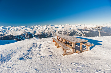 Wall Mural - Picnic table on a snowy mountain top