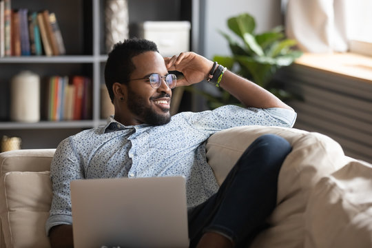 Happy young african american man stretching back, enjoying free leisure weekend time alone on sofa with computer. Smiling multiracial freelance guy distracted from job study, looking at window.