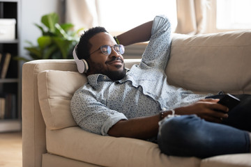 Tranquil carefree young african american man lying on comfy couch, wearing modern wireless headphones, listening to favorite classic music online, feeling peaceful mindful alone in living room.
