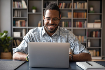 Front view head shot young smiling african american businessman in eyewear looking at laptop screen, reading pleasant messages in social networks, working on computer sitting at table in office home.