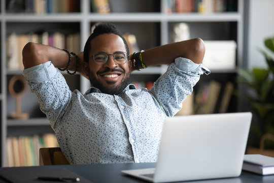 Head shot satisfied calm smiling young african american businessman folded arms behind head, reclining on chair, relaxing, enjoying break pause time alone in office or home, looking at camera.
