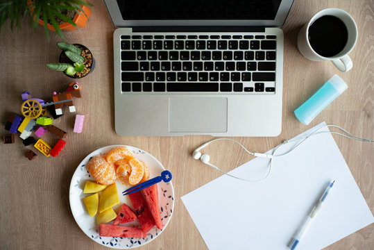 Top view of laptop on the wooden desk with stationaries and coffee with mixed fruit. Work from home. Quarantine at home