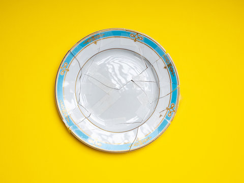 Directly Above Shot Of Broken Plate Over Yellow Background