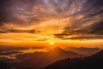 Zelfklevend Fotobehang Diepbruine High angle view of a breathtaking sunset scenery in the golden cloudy sky over the hills