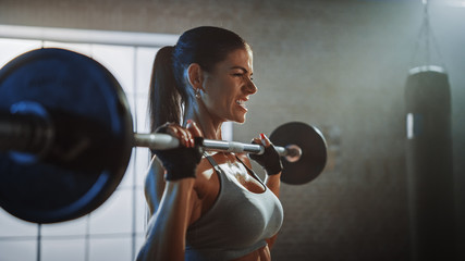 Athletic Beautiful Woman Does Overhead Lift with a Barbell in the Gym. Gorgeous Female Professional Bodybuilder Does Weight Lift Workout Exercises in the Hardcore Training Facility.