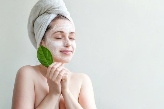 Minimal beauty portrait woman girl in towel on head applying white nourishing mask or creme on face, green leaf in hand isolated white background. Skincare cleansing eco organic cosmetic spa concept.